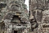 Mossy Stone Face Of Ancient Buddhist Temple Bayon In Angkor Wat Complex, Cambodia. Ancient Architect poster