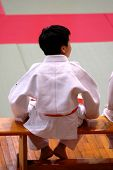 pic of shotokan  - A karate kid sitting on bench and watching the competition - JPG