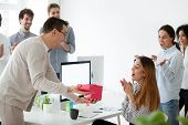 Excited Male Worker Congratulating Shocked Female Employee With Special Occasion, Presenting Gift Bo poster