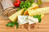 Top View Of Pieces Of Different Soft, Semi-soft, Medium-hard And Hard Cheese Among Of Brown Bread, N poster