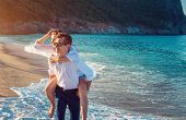 Young Happy Couple In Love Having Fun On Tropical Beach In The Morning. People Chilling And Enjoying poster
