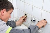 stock photo of plumbing  - Plumber fixing pipeline with tool in handsand checking leaking - JPG