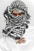 stock photo of fundamentalist  - Arab muslin in white cloth and kaffiyeh shemagh head gear with stern threatening look - JPG