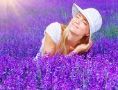 Pretty woman sitting on lavender field at sunny day, beautiful female on purple flowers meadow, chee poster
