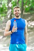 Athlete Drinks Water After Training In Park On Sunny Day. Man Athletic Attractive Appearance Holds W poster