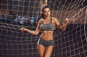 Young Beautiful Tanned Sexy Sporty Woman In Gray Top And Small Shorts Posing Against Soccer Net On S poster