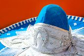 charro mariachi blue mexican hat detail over orange background in Mexico