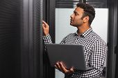 Server Room. Focused It Guy Using Laptop And Pointing At Hardware poster