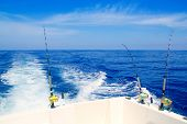 boat fishing trolling in deep blue sea with rods and reels