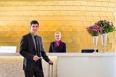 Man in Hotel check in at reception or front office being given key card poster