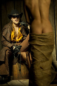 stock photo of nacked  - Cowboy looking at naced bondwoman against wooden background - JPG