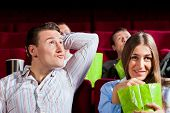 Couple in cinema watching a movie, they eating popcorn