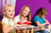 Children - sisters - making music at home, they are practicing playing guitar, bongo and flute as instruments