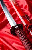 Japanese sword takana on red satin background