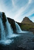 Famous Icelandic Waterfalls With Looming Kirkjufell Arrowhead Mountain In Background. Blue Sky And C poster