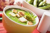 Thick green pea vegetable soup with croutons