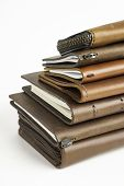 A Stack Of Leather-bound Journals, Notebooks, Cases And Wallets Set On A Plain White Background. poster
