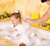 Mother and happy child washing in bubble bath .