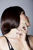portrait of a beautiful woman in short brunette bob with neat clean hair on studio background - focu