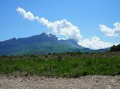 White Clouds Cover The Tops Of The Rocky Mountains. Near The Pond With Clear Mountain Clear Water An poster