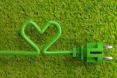 Green Power Cord With Heart Shaped Power Cable On Grass Background With Copy Space - Eco Or Green Po poster