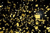 Gold confetti falling against a black background