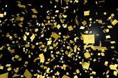 Gold confetti falling against a black background