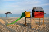 Landscape and playground on island Corsica with wicker parasols poster