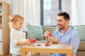 family, fatherhood and childhood concept - happy father and little daughter with toy crockery playin poster