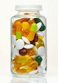 Glass bottle full of colorful pills, tablets, vitamins, drugs, omega 3 fish oil, gel capsules, medic poster