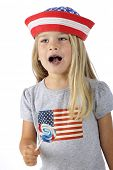 An adorable preschooler in American patriotic clothes.  She's paused licking her sucker to sing.  (Mouth is blue for the sucker.)  On a white background.