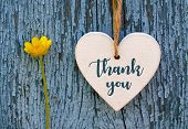 Thank You Or Thanks Greeting Card With Yellow Flower And Decorative White Heart On Blue Wooden Backg poster