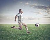 Jogador de futebol, correndo atrás de uma bola de futebol em um Prado