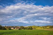Bavarian spring rural landscape with green field and town in background, Germany, Europe poster