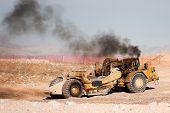 Heavy Construction Equipment Scraper Emitting Diesel Fumes poster