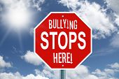 image of stop bully  - Red bullying stops here stop sign with white text on a cloud background - JPG