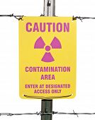 Caution radioactive contamination warning sign with barb wire fence isolated.