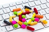 many pills and computer keyboard. photo icon for online and internet pharmacy.