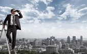 pic of urbanization  - Businessman with binoculars spying on competitors - JPG