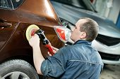 stock photo of auto garage  - auto mechanic worker polishing bumper car at automobile repair and renew service station shop by power buffer machine - JPG