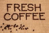 Fresh coffee bean sign in letter word form with loose beans on a hessian background.