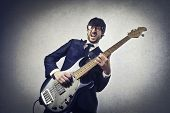 stock photo of ironic  - young musician playing bass - JPG