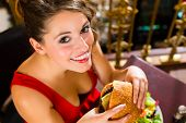 stock photo of table manners  - Young woman in a fine dining restaurant eat a hamburger - JPG