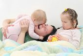 Família feliz. Jovem mãe brincar com seus filhos na cama.