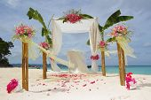 picture of gazebo  - wedding arch and set up with flowers on tropical beach - JPG