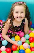 Happy Little Girl Sitting In Colourful Balls