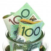 Australian money in jar, over white background.  One hundred dollar bills.