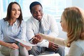 Bild sicher Kollegen betrachten ihres Geschäftspartners bietet ihnen Papier bei REGIERU anmelden