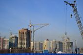 Construction works on a highrise buildings with cranes over a blue sky.
