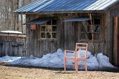 stock photo of shacks  - Old shack with a blue roof with a pink chair